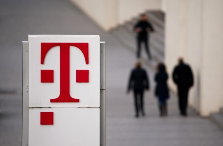 People walk past the logo of German telecommunications giant Deutsche Telekom AG seen at the Telekom's headquarters in Bonn February 25, 2016.    REUTERS/Wolfgang Rattay/File Photo
